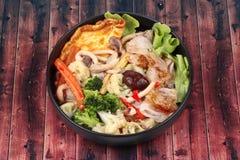 油煎的大面条用煎蛋卷冠上了在汤的混杂的菜 免版税库存照片