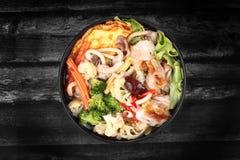 油煎的大面条用煎蛋卷冠上了在汤的混杂的菜 免版税库存图片