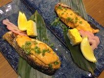 油煎的平底锅在餐馆, m烤了三文鱼内圆角上面用辣热的单乳脂状的调味汁和甜鸡蛋在日本式在蓝色板材 库存照片