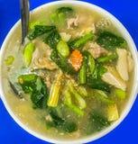 油煎的平的宽面条用猪肉和无头甘蓝在泰国乳脂状的小汤的调味汁:在白色碗的Guaitiao Rad Na在蓝色桌背景 免版税库存图片