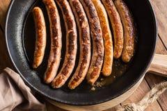 油煎的或烤香肠品种与开胃金黄外壳的在铁熔铸了平底锅 免版税库存图片