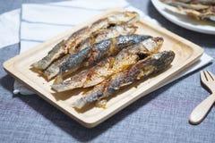 油煎的梭鱼鱼在木盘子服务 库存图片