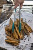 油煎的棒子面涂上了在报纸堆积的鱼片 免版税库存图片