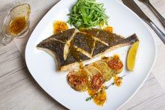 油煎的比目鱼用夏南瓜、蕃茄和芝麻菜 图库摄影