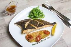 油煎的比目鱼用夏南瓜、蕃茄和芝麻菜 免版税库存图片