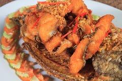 油煎的河鱼用大蒜和胡椒 图库摄影