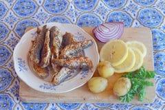 油煎的波儿地克的鲱鱼、土豆、柠檬、红洋葱和同水准板材  免版税库存图片