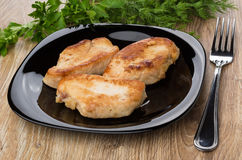 油煎的火鸡肉片断在板材、叉子和绿色的 免版税库存照片