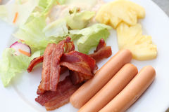 油煎的烟肉、香肠和菜 库存照片