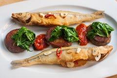 油煎的熔炼用土豆菠菜留下大蒜 在一块白色板材的两条金黄开胃鱼 传统地中海 图库摄影