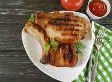 油煎的牛排猪肉准备了在木背景的番茄酱蕃茄 库存图片
