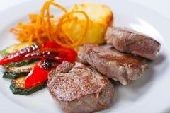 油煎的牛排用土豆、胡椒和夏南瓜 免版税库存图片