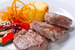 油煎的牛排用土豆、胡椒和夏南瓜 免版税库存照片