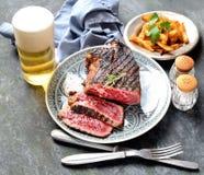 油煎的牛排用在一块板材、香料、芯片、啤酒、刀子和叉子的迷迭香在黑暗的背景 库存图片