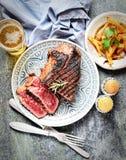 油煎的牛排用在一块板材、香料、芯片、啤酒、刀子和叉子的迷迭香在黑暗的背景 免版税库存照片