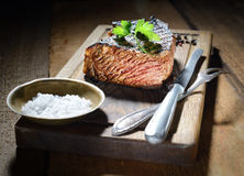油煎的牛排用芳香香料,与一道配菜的盘,刀子和叉子在一个木板 库存照片