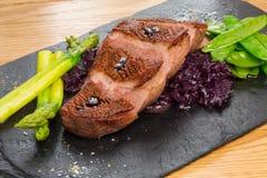 油煎的牛舌肉用甜菜根和豌豆荚,芦笋 免版税库存照片