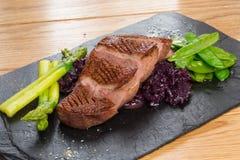 油煎的牛舌肉用甜菜根和豌豆荚,芦笋 库存图片
