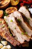 油煎的猪排用大蒜和辣椒和被烘烤的土豆 库存照片