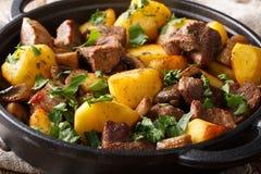 油煎的猪肉主菜用土豆和蘑菇特写镜头在平底锅 ?? 免版税库存照片