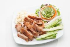 油煎的猪肉供食与各种各样的菜 免版税库存图片
