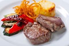 油煎的猪肉牛排用土豆、胡椒和夏南瓜 免版税库存照片