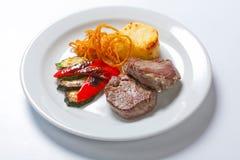 油煎的猪肉牛排用土豆、胡椒和夏南瓜 库存照片