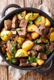 油煎的猪肉用土豆和蘑菇特写镜头在平底锅 r 免版税库存图片