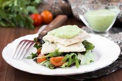 油煎的白色鱼内圆角用蕃茄沙拉,芝麻菜,草本 库存图片