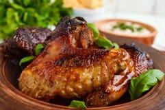 油煎的翼低头,在蜂蜜釉的鸡在轻的背景的黏土碗 免版税图库摄影