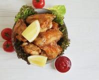 油煎的翼柠檬,在一道木烤背景热的开胃菜烘烤的烹调 图库摄影
