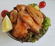 油煎的翼柠檬,烹调在一道木烤背景热的开胃菜吃 免版税库存照片