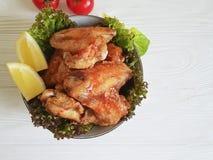 油煎的翼柠檬,烹调在一道木烤背景热的开胃菜的被烘烤的营养 免版税库存图片