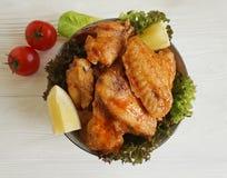 油煎的翼柠檬,烹调在一道木烤背景热的开胃菜 库存照片