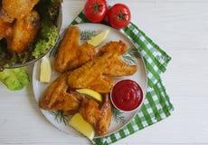 油煎的翼,烹调在一道木烤背景热的开胃菜 免版税库存图片