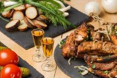 油煎的肉、土豆、绿色、菜在板岩板材和两个小玻璃用科涅克白兰地 免版税库存图片