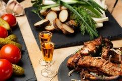 油煎的肉、土豆、绿色、菜在黑板岩板材和两个小玻璃用科涅克白兰地 库存图片