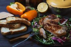 油煎的肉、牛排片断在一把叉子的用沙拉,草本、胡椒、柠檬和油煎方型小面包片在黑暗的木背景 t的背景 图库摄影