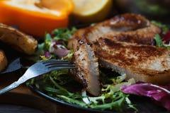 油煎的肉、牛排片断在一把叉子的用沙拉,草本、胡椒、柠檬和油煎方型小面包片在黑暗的木背景 t的背景 库存照片