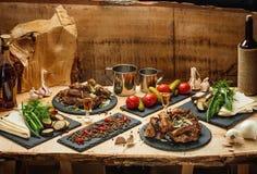 油煎的肉、用卤汁泡的菜、土豆、绿色、spetsiin板岩黑色的盘子和一个科涅克白兰地瓶有两射击的 库存图片