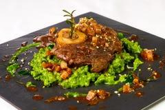 油煎的肉片在绿色调味汁的在轻的backg的石板材 免版税图库摄影