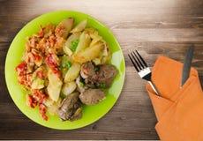 油煎的肝脏用土豆和被炖的蕃茄 免版税库存照片