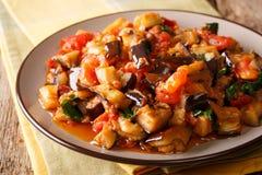 油煎的茄子、蕃茄和大蒜夏天温暖的沙拉与sp 免版税库存图片