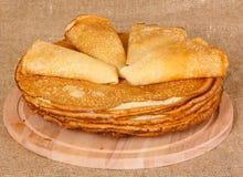 油煎的薄煎饼在一个木切板说谎 免版税库存图片