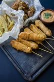 油煎的薯条,Ð ¡橙色狗和圆白菜炸丸子和土豆用调味汁和番茄酱用新鲜蔬菜装饰和 库存照片