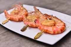 油煎的虾加调料烘烤在白色板材的串串在木ta 免版税库存照片