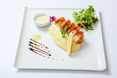 油煎的虾用土豆泥用在一块白色板材的调味汁装饰用新鲜的莴苣 混乱油炸物虾 免版税库存图片