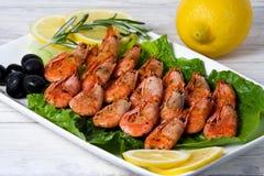 油煎的虾用香料、橄榄和柠檬 免版税库存图片