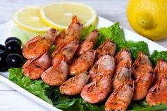 油煎的虾用香料、橄榄和柠檬 免版税库存照片