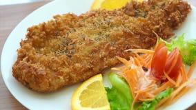 油煎的被打击的鱼和五颜六色的沙拉